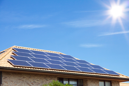 Photovoltaics on the roof of a residential building in front of amazing blue sky with copyspace
