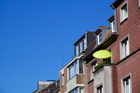 Row of houses, one with a sunshade on balcony for a relaxed evening, against a blue sky in Aachen, Germany Stock Photo