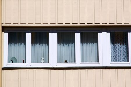 Row of windows with closed curtains in beige facade