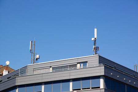 Exterior view of the upper floor and roof of a modern flat roof urban house with communication antennae on the rooftop against a blue sky