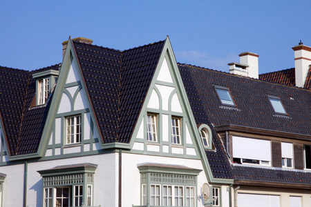 Historical architecture in De Haan, Belgium in Belle Epoque style with an interesting dark roofed townhouse against a blue sky