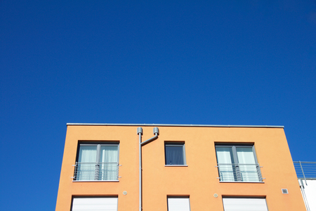 Closeup of an orange apartment building against a blue sky