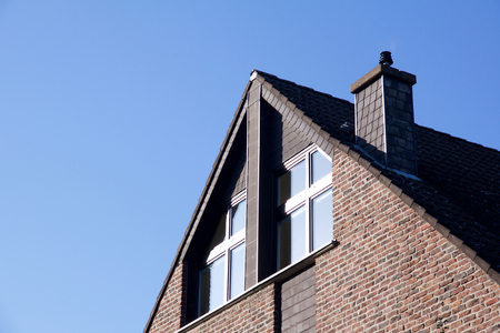 House with red bricks and windows next to chimney under roof Stock Photo