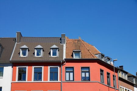 Beautiful red house with dormer windows against a blue sky in summer, some shutters down Zdjęcie Seryjne - 78451785