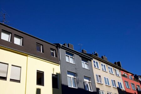 Row of colourful houses against a blue sky in Aachen, Germany Stock Photo