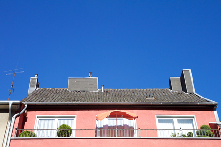 Red house with sunshade on balcony and chimney on roof against a blue sky in Aachen, Germany Stock Photo
