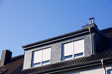 Closeup view on a house with dormer windows, shutter down