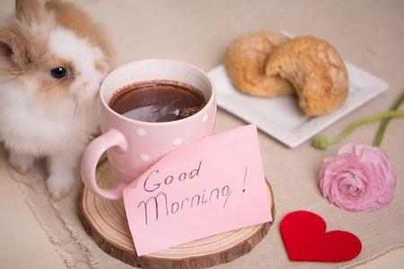 animalitos tiernos: Conejo del bebé en la mesa durante el desayuno. Taza de té, carta del mensaje, flores ranúnculo y de galletas en la placa.