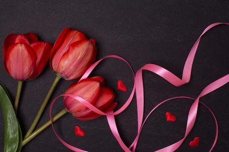 Empty clean black chalkboard with red tulips and hearts. Top view. Valentines day card or template for your design.