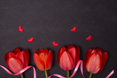 petites fleurs: Empty clean black chalkboard with red tulips and hearts. Top view. Valentines day card or template for your design.