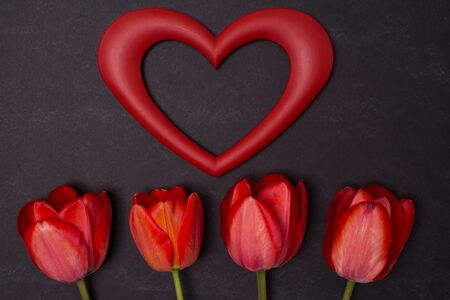 clean heart: Empty clean black chalkboard with red tulips and empty heart frame. Top view with copy space. Valentines day card or template for your design.