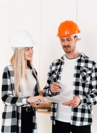 Two designers in helmets and plaid shirts discuss a list of additions on site. The concept of building interiors. Interior designers discussing changes against a white wall.
