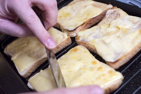 Pair of hands from unidentifiable person preparing four square slices of bread grilled with melted cheese
