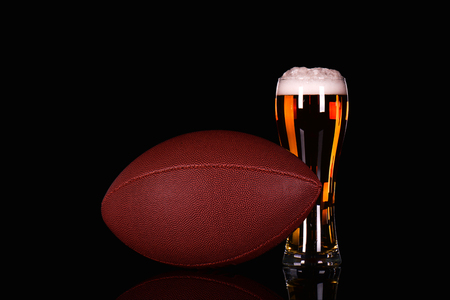 6 pack beer: Beer glass with dark beer foam and American football ball on black background.