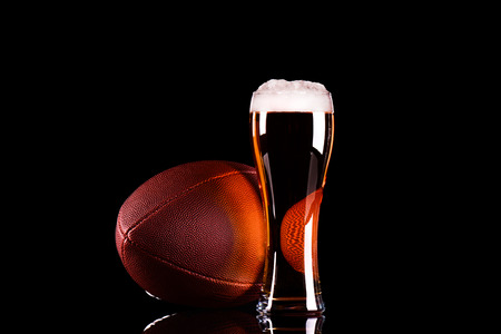 Beer glass with dark beer foam and American football ball on black background Stock Photo
