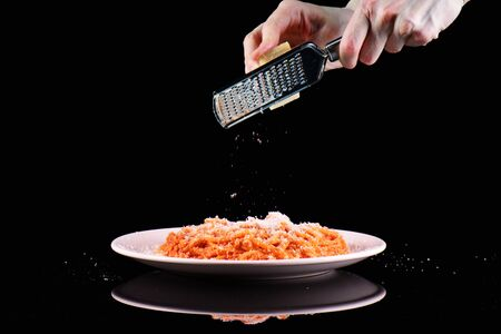 Rub grating Parmesan cheese on pasta spaghetti macaroni plate. Hands grate cheese on black background.