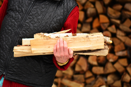Old woman with firewood in the hands in the village. Stock Photo