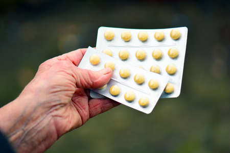 Old woman holding pills in her hand. Elderly female with pills or pharmaceutical meds