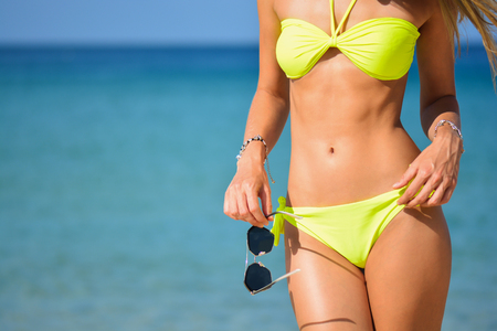 beautiful fit young woman in sexy yellow bikini at the beach. Girl with sunglasses, summer time near blue sea. Girls abs