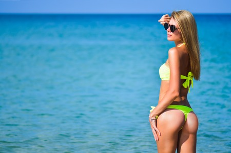 beautiful fit young woman in sexy yellow bikini at the beach. Girl in swimsuit and sunglasses, summer time near blue sea