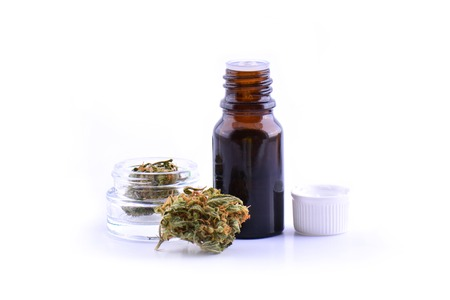 Medicinal marijuana cannabis with extract oil in a bottle. cannabis CBD oil hemp products. Cannabis oil extracts in jar.