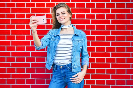 Young pretty woman taking selfie outdoors - Female summer fashion portrait - Teenager student holding mobile phone for selfi photo next to brick wall background Stock Photo