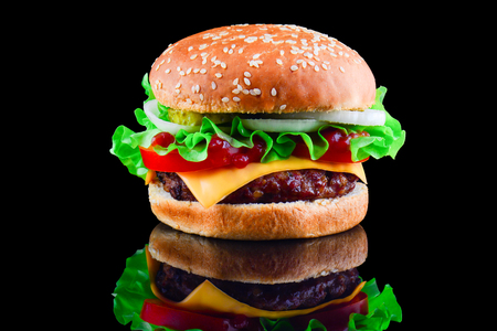 Big tasty hamburger or cheeseburger on black background with grilled meat, cheese, tomato, bacon, onion. Burger closeup