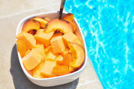 fruit in a bowl by the pool. Fruit salad, healthy breakfast. Colorful fruit peach and melon, summer concept.
