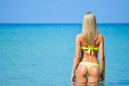 beautiful fit young woman in sexy yellow bikini at the beach. Girl in swimsuit, summer time near blue sea. Beautiful fit young woman butt in sexy yellow bikini