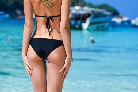 Sexy woman buttocks on tropical beach background near ocean. close up outdoor shot of young woman in black bikini, sunbathing at sea shore. Black bikini on ocean background.