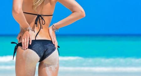 Sexy Frau auf tropischem Strandhintergrund nahe Ozean. Junge Frau im schwarzen Bikini, Sonnenbaden auf See. Mädchen am Strand. Reise-Urlaub-Konzept. Mädchen mit gebräunter Körper. Tropische Insel. Standard-Bild