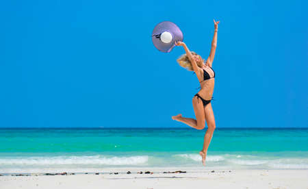 Woman in bikini and sun hat relaxing at sunny beach Slim girl jumping near blue sea. Remote tropical beaches and countries. Travel concept