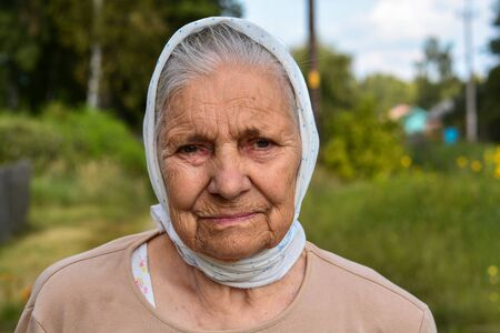Portrait of old lonly woman in headscarf. Elderly woman