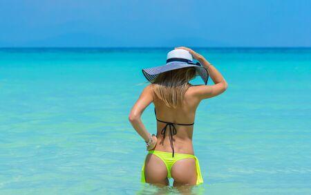 Beautiful fit young woman in sexy yellow bikini and hat the beach. Girl in swimsuit, summer time near blue sea. Beautiful fit young woman butt in sexy yellow bikini. Archivio Fotografico - 137963193