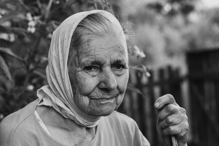 Black and white portrait of old lonly woman in headscarf. Elderly woman.
