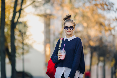 Pretty hipster teen with red bag drinks milkshake from a plastic cup walking street between buildings. Cute girl in sunglasses drinks a drink through a straw. 写真素材
