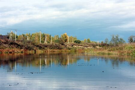 Autumn landscape. The river in which is reflected sky and clouds Stock Photo