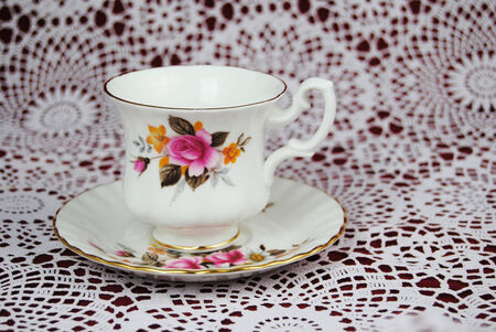 Antique cup and saucer with flowers and a golden line photo