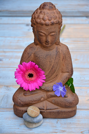 musing: Buddha statue with zen stones and flowers Stock Photo