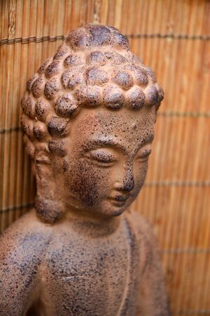 musing: Buddha statue with zen stones and bamboo reed background