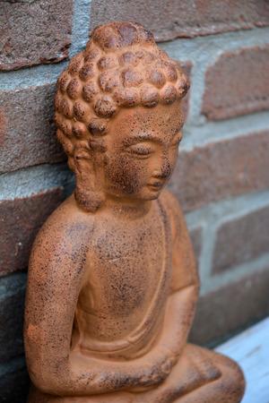 Buddha statue with bricks background photo