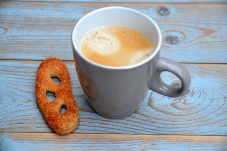symbolically: Coffee with pretzel cookie on a wooden background