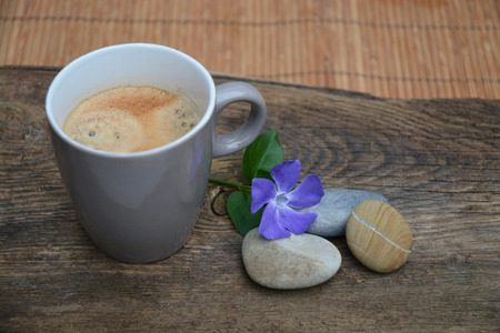 balance symbolic: coffee mug  with three zen stones on Brown old  with purple flower Stock Photo