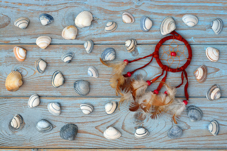 Bordeaux dark red dream catcher with feathers on old wooden background with sea shells Stock Photo