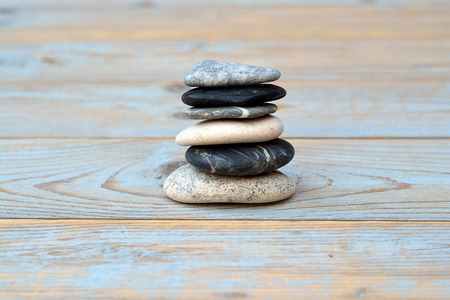emty: crain gray black zen stones on gray, blue, knotted old wooden shelves background with emty copyspace