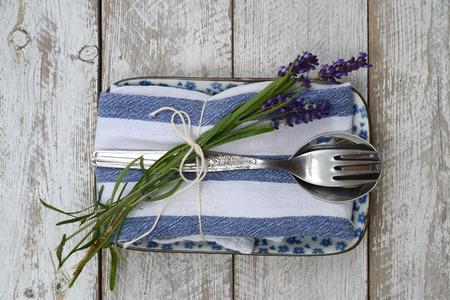 stile country: posate d'argento su un tovagliolo bianco blu con decorazioni lavanda e copyspace vuoto in stile country d'epoca