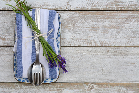 country style: silver cutlery on a blue white napkin with lavender decoration and empty copyspace in vintage country style