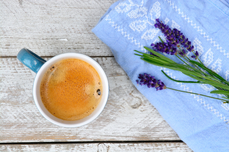 residual: Blue coffee cup and lavender on a old white wooden shelves background with empty copyspace with embroidery napkin in vintage style