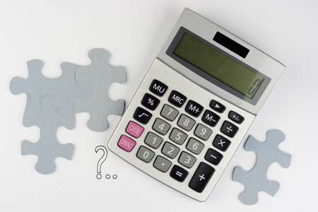 Calculator on a white gray background with empty copyspace puzzle pieces for finance administration 스톡 콘텐츠
