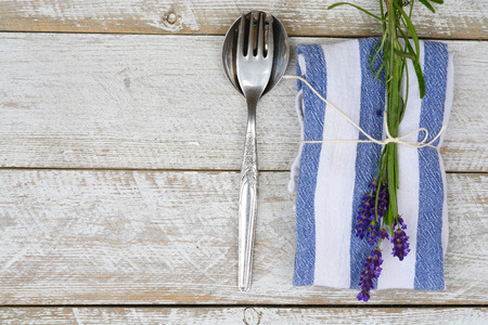 stile country: silver cutlery on a blue white napkin with lavender decoration and empty copyspace in vintage country style